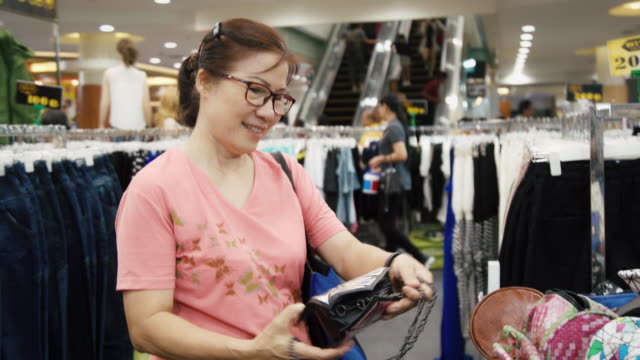 Asian Woman Family Choosing and Buying Shopping Bag and Clothes at the Store Shop.