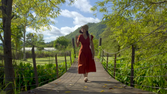 Asian woman Feel free Run in the vast fields of flowers on a clear day In the forest.