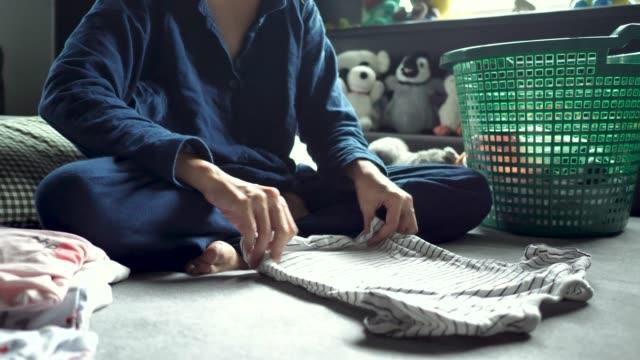 アジアの女性は、ベッドの上の洗濯物の折りたたみ。 - 楽しい 洗濯点の映像素材/bロール