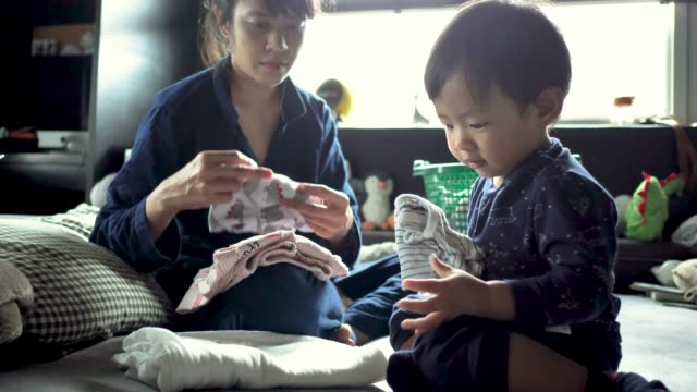 Asian woman folding laundry watching playful baby boy playing. video