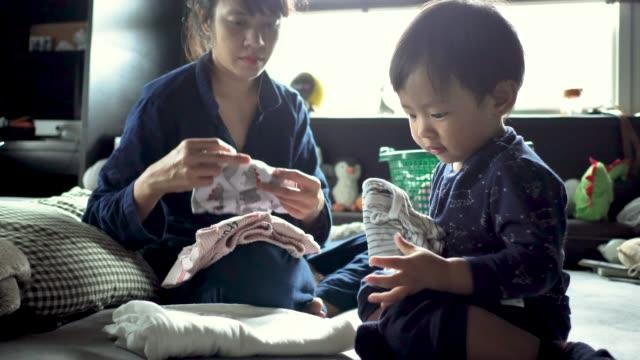 vídeos de stock, filmes e b-roll de mulher asiática dobrar roupa assistindo menino brincalhão jogando. - afazeres domésticos