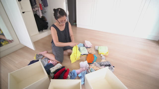 Asian woman folding the baby cloth in the dressing room at home 4K Video by LS Dolly right Camera and selective focus with color grading of Asian woman folding the baby cloth in the dressing room at home laundry basket stock videos & royalty-free footage