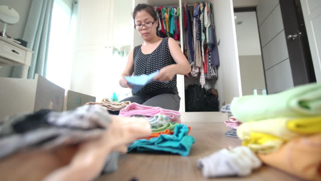 Asian woman folding the baby cloth in the dressing room at home 4K Video by LS Still Shot and selective focus with color grading of Asian woman folding the baby cloth in the dressing room at home laundry basket stock videos & royalty-free footage