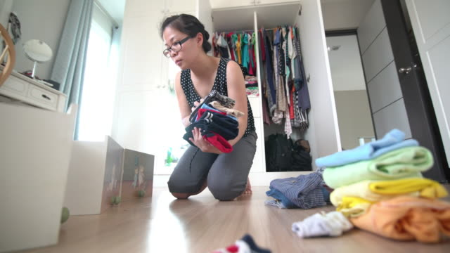 Asian woman folding the baby cloth in the dressing room at home 4K Video by MS Dolly In Camera and selective focus with color grading of Asian woman folding the baby cloth in the dressing room at home laundry basket stock videos & royalty-free footage
