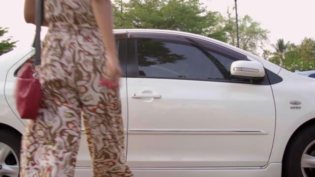 vídeos y material grabado en eventos de stock de mujer asiática entrando en el coche blanco. - manija