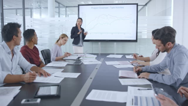 Asian woman giving a financial presentation in the conference room