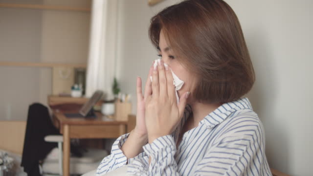 Asian woman got flu sneezing in tissue sit on bed