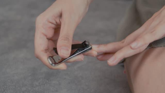 asiatische frau hand schneiden auf ihre fingernägel zu hause mit nagel clipper - fingernagel stock-videos und b-roll-filmmaterial