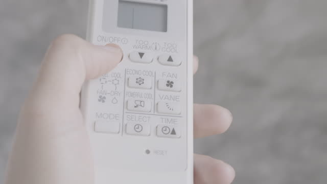 Asian woman hand is using remote control air conditioner Asian woman hand is using remote control air conditioner power supply stock videos & royalty-free footage