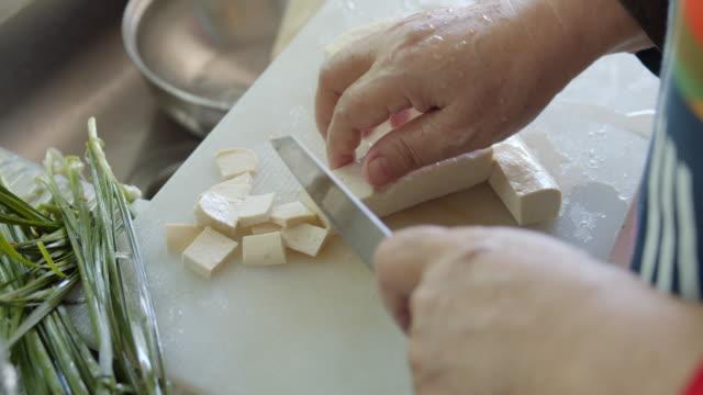 asian woman hand slicing a tofu at the kitchen - tajska kuchnia filmów i materiałów b-roll