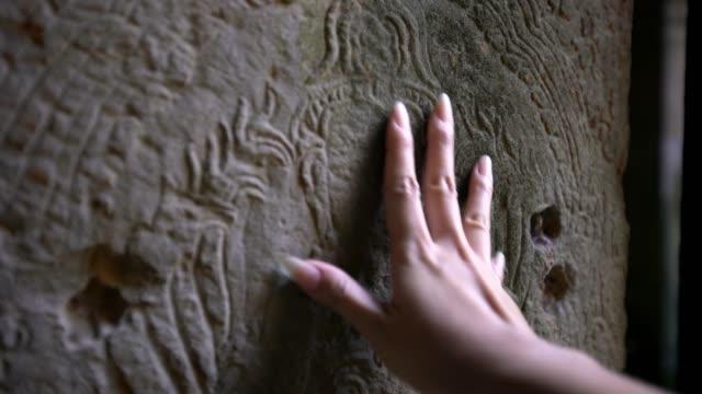 vídeos de stock, filmes e b-roll de 4k mulher asiática toca mão esculturas antigas adornam nas paredes do templo camboja. - relevo
