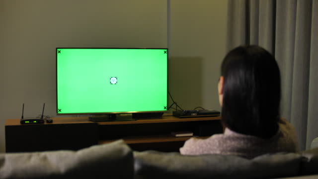 Asian Woman hand with TV remote switching channels on a green screen TV Asian Woman hand with TV remote switching channels on a green screen TV changing channels stock videos & royalty-free footage