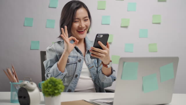 Asian woman happy looking at tablet reading news showing OK sign at home office. WFH. Work from home.