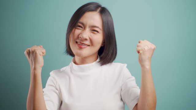 Asian woman happy smiling and make winning gesture standing isolated over blue background. 4K video. Emotional conceps.