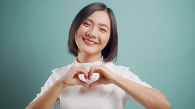 Asian woman happy smiling in love making heart shape by hands and looking at camera standing isolated over blue background. 4K video. Emotional conceps.