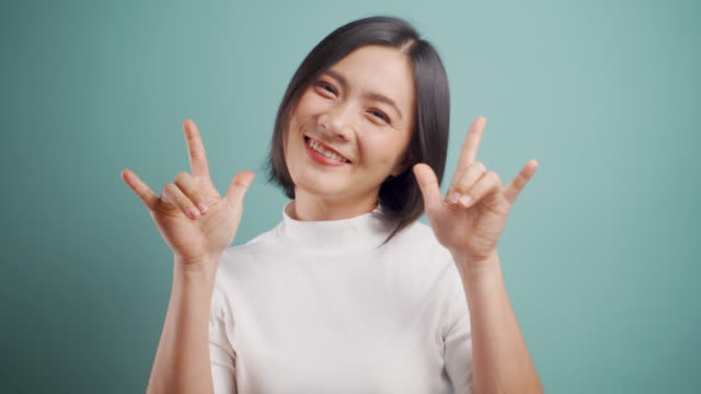 Asian woman happy smiling in love showing i love you sign language and looking at camera standing isolated over blue background. 4K video. Emotional conceps.