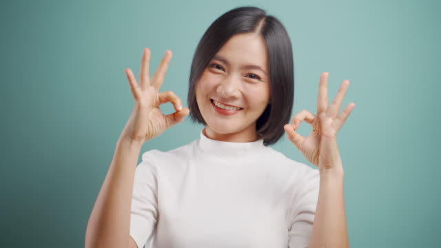 Asian woman happy smiling showing hands in OK sign language and standing isolated over blue background. 4K video. Emotional conceps. video