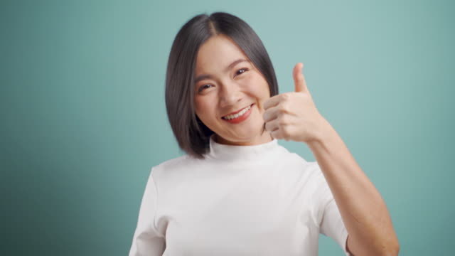 Asian woman happy smiling showing thumb up and standing isolated over blue background. 4K video. Emotional conceps. video