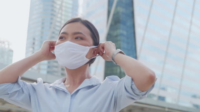 Asian woman happy smiling wearing protective face mask. New lifestyle with Corona Virus COVID-19. video