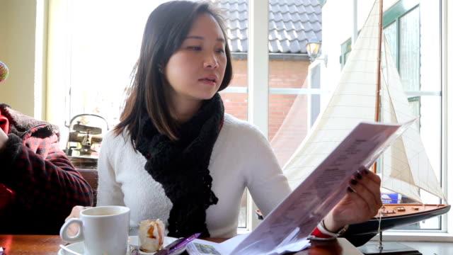 Asian woman holding menu sheet for order Asian woman holding menu sheet for order in restaurant menu stock videos & royalty-free footage