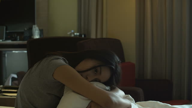 4K: Asian woman hugging her knees up to her chest in bed video