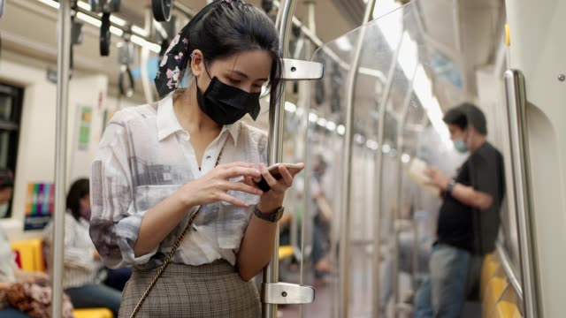 asian woman in black protective mask using smartphone, stand leaning on the pole, covid-19 new normal, woman in subway metro, self protection on public transport, - hand on glass covid video stock e b–roll