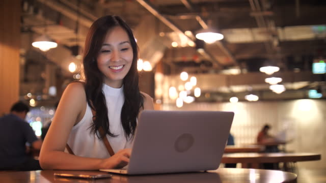 Asian Woman in Casual Clothing using Laptop for her work