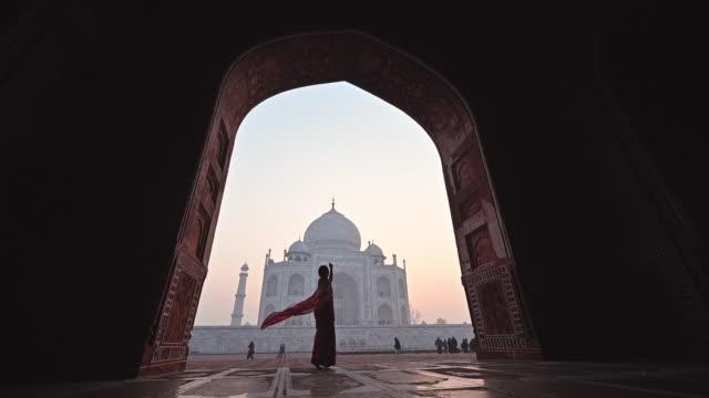 Asian woman in dressing red saree indian traditional dress dancing inTaj Mahal, Agra, India