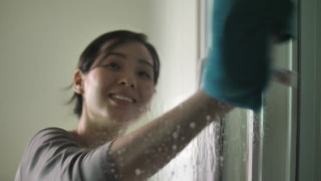 asian woman in gloves cleaning window with rag - stay at home parent stock videos & royalty-free footage