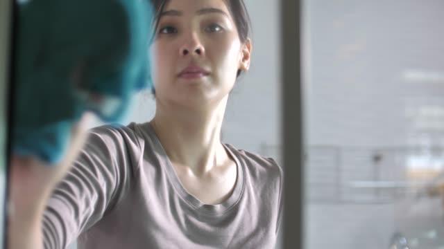 アジアの女性で手袋クリーニングウィンドウとともに rag - きれいにする点の映像素材/bロール
