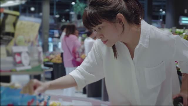 asiatisk kvinna i livsmedelsbutik - köpnarkoman bildbanksvideor och videomaterial från bakom kulisserna