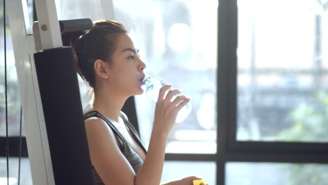 asian woman in gym drinking energy drink - reggiseno sportivo video stock e b–roll