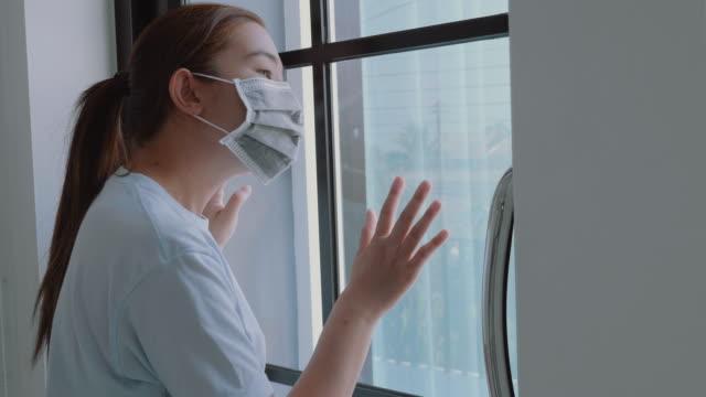 donna asiatica in isolamento a casa per epidemia di virus coronavirus indossando una maschera facciale quarantena se stessa - hand on glass covid video stock e b–roll
