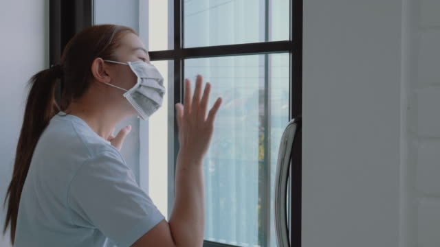 asian woman in isolation at home for virus outbreak coronavirus wearing a face mask quarantine herself - hand on glass covid video stock e b–roll
