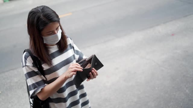 Asian woman in mask looking at wallet purse, female standing on the street side, new normal lifestyle outdoor shot, covid-19 pandemic crisis, preventing virus, social distancing, female take out money outdoor shot, NEW NORMAL life concept, wear mask hot pockets stock videos & royalty-free footage