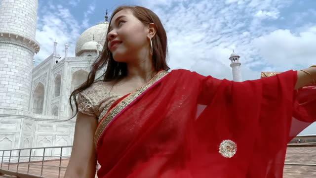 Asian woman in red saree/sari in the Taj Mahal, Agra, Uttar Pradesh, India