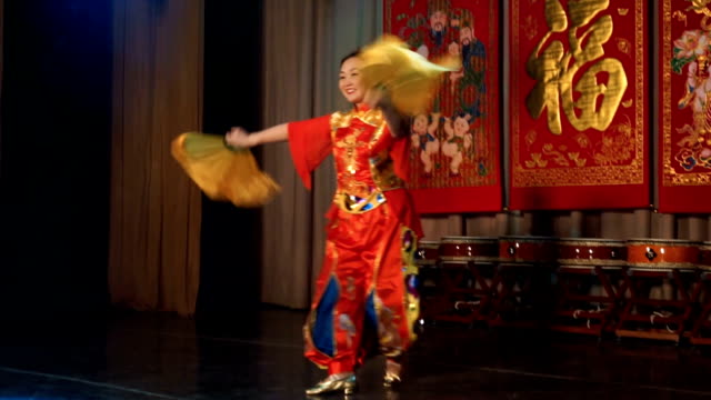 vídeos de stock e filmes b-roll de asian woman in traditional red chinese costume performs dance with big yellow fans. - cultura chinesa