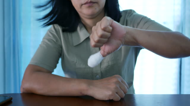 Asian woman injured finger with bandage