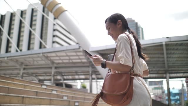 stockvideo's en b-roll-footage met aziatische vrouw is chatten online met vrienden met behulp van slimme telefoon en wandelen in het kantoorgebouw - oost azië
