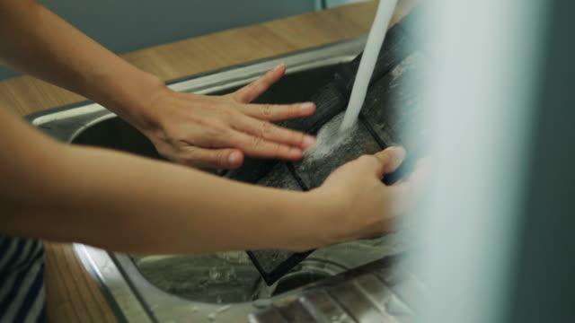 asiatisk kvinna är rengöring luftar villkorar på sitt rum på helgen - kvinna ventilationssystem bildbanksvideor och videomaterial från bakom kulisserna