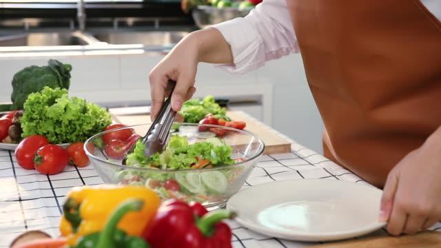 아시아 여성은 샐러드 그릇에 샐러드를 만들 준비가 된 재료를 붓고 있습니다. - 찰리스 스톡 비디오 및 b-롤 화면