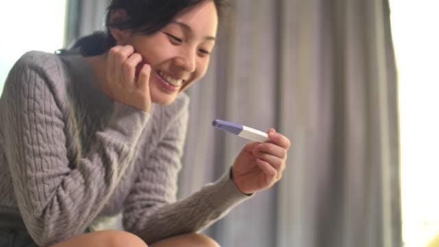vídeos y material grabado en eventos de stock de mujer asiática está embarazada usando la prueba de embarazo, feliz sentimiento - planificación familiar