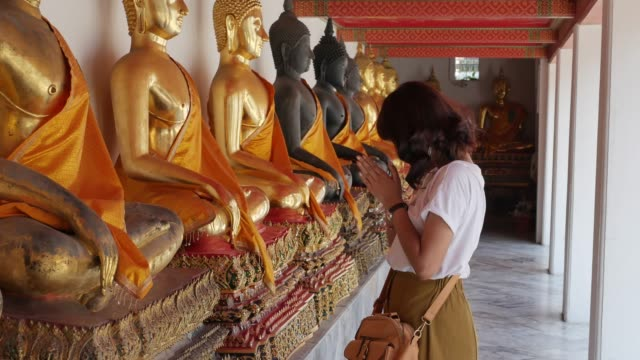 Asian woman is worshiping Buddha statue in Pho temple in Bangkok, Thailand.