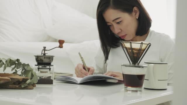asiatische frau ist ihre arbeit schreiben. - schwarzer kaffee stock-videos und b-roll-filmmaterial