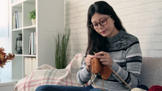 asian woman knitting and looking the weather