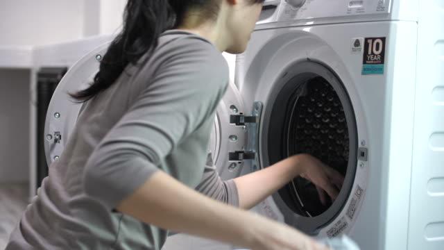 アジアの女性は自宅で洗濯 - 楽しい 洗濯点の映像素材/bロール