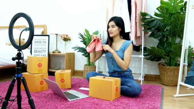 4k. asiatische frau live-streaming für den verkauf von schuh, mode-accessoires online auf social media per handy aus dem schlafzimmer zu hause. inhaber eines kleinunternehmens, das von zu hause aus während der selbstisolierung arbeitet - bloggen stock-videos und b-roll-filmmaterial