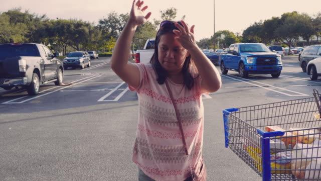 Sacs d'épicerie asiatique femme chargement arrière de la voiture - Vidéo