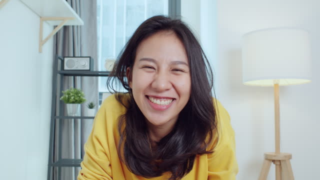 Asian woman look at camera, greeting and talk to friends on video call online meeting at home. Remote internet conference, social distancing, new normal lifestyle 2020 concept