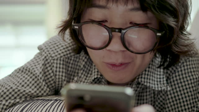 Asian Woman looking on smart phone for Social Media video